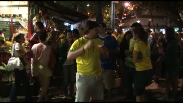 vidéos et rushes de soccer fans cheering and hanging out in front of bar / rio de janeiro, brazil - 2010
