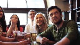 soccer fans watching football match at bar or pub