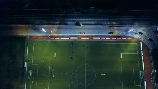 vídeos de stock, filmes e b-roll de campo de futebol à noite - vista aérea - campo de futebol