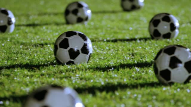 vídeos de stock, filmes e b-roll de cu pan soccer field covered in soccer balls at night - campo de futebol