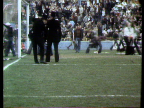 stockvideo's en b-roll-footage met soccer finance council to give money to local clubs itn lib ms fans onto pich pan leftright - 1978