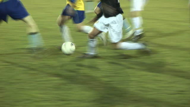 soccer / football match under floodlights on grass pitch - tackling stock videos and b-roll footage