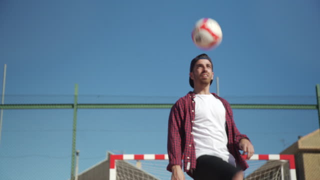 soccer football played by young adult. juggling ball. street game with casual clothes. for the love of the game: soccer/futbol - baseball cap stock videos & royalty-free footage