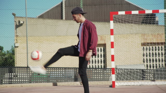 soccer football played by young adult. juggling ball. street game with casual clothes. for the love of the game: soccer/futbol - juggling stock videos & royalty-free footage