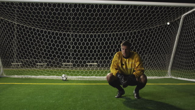 slo mo. soccer goalie crouches down inside a soccer net and outs his head in his hands after the other team scores during a nighttime match - verlust stock-videos und b-roll-filmmaterial