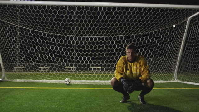 slo mo. soccer goalie crouches down inside a soccer net and outs his head in his hands after the other team scores during a nighttime match - soccer glove stock videos and b-roll footage