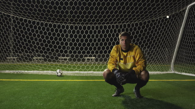 slo mo. soccer goalie crouches down inside a soccer net on a soccer field during a nighttime match and looks at the camera - soccer glove stock videos and b-roll footage