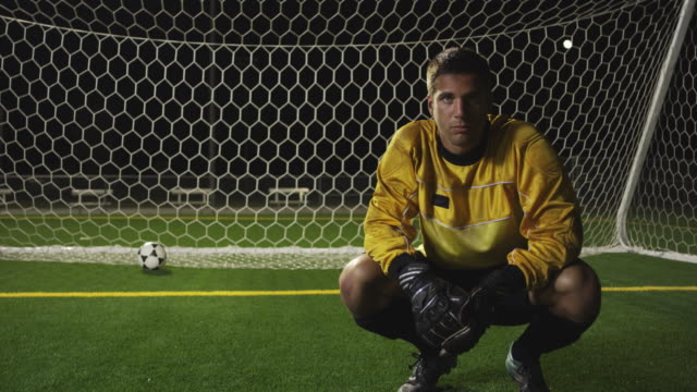 SLO MO. Soccer goalie crouches down inside a soccer net on a soccer field during a nighttime match and looks at the camera