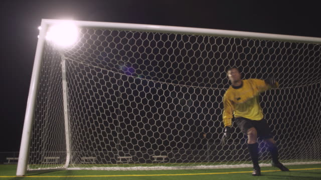 slo mo. soccer goalie dives to defend goal during a nighttime match inside a stadium - soccer goal stock videos and b-roll footage