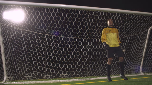 A goalie shuffles his feet before diving to save the soccer ball from going in the net.