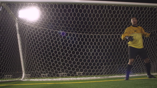 A goaltender shuffles his feet before diving to defend the soccer goal.