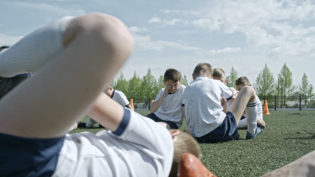 Soccer kids stretching on green stadium field at summer day