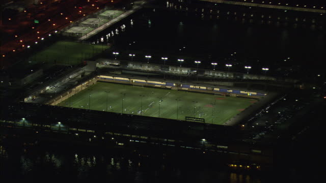 AERIAL Soccer match on Pier 4 field at night / New York City, New York, USA