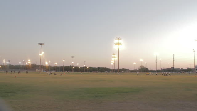 stockvideo's en b-roll-footage met soccer matches and drills going on during dusk with stadium lights. - schemering