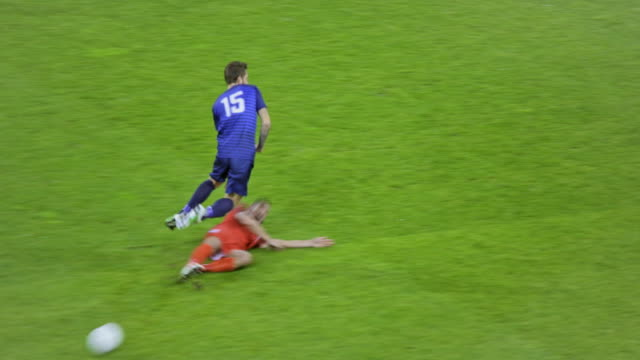 stockvideo's en b-roll-footage met soccer player bringing his opponent to the ground at a soccer match - sportwedstrijd