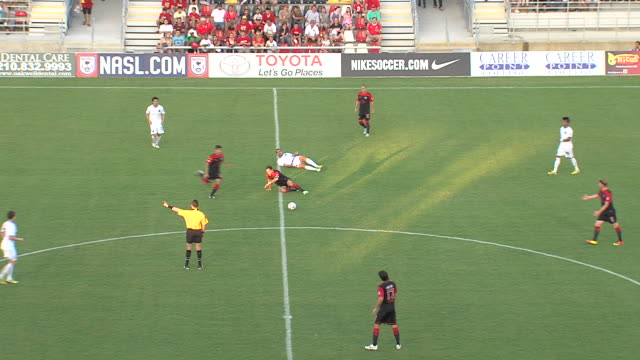 a soccer player commits a foul and then game resumes before another foul is commited - tackling stock videos and b-roll footage