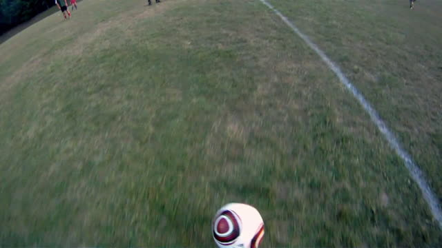A soccer player dribbles and then kicks the ball toward the goal.