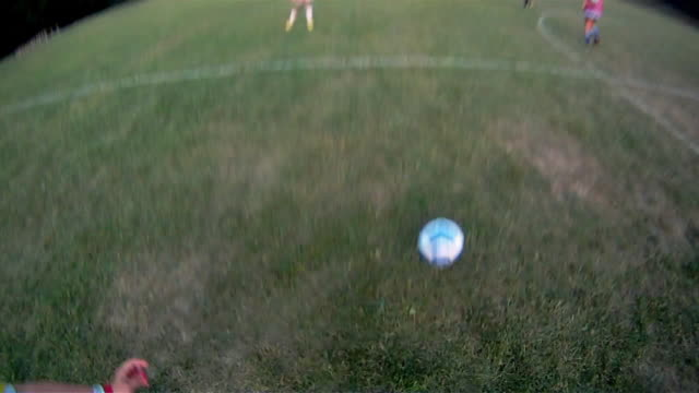 A soccer player dribbles the ball and makes a shot on goal.