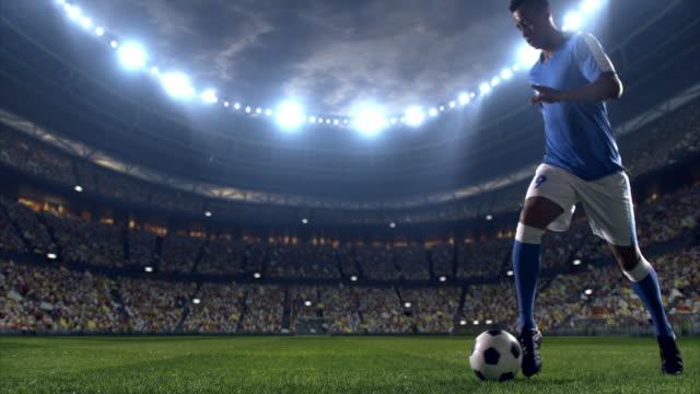 vídeos de stock, filmes e b-roll de jogador de futebol com uma bola em dribles no campo - passe de bola