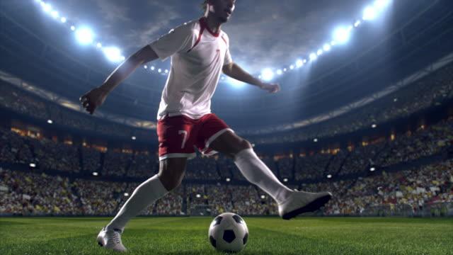 Fotbollspelare dribblingar en boll på fältet
