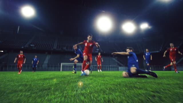 vídeos de stock e filmes b-roll de slo mo soccer player dribbling his opponent at a night match - football