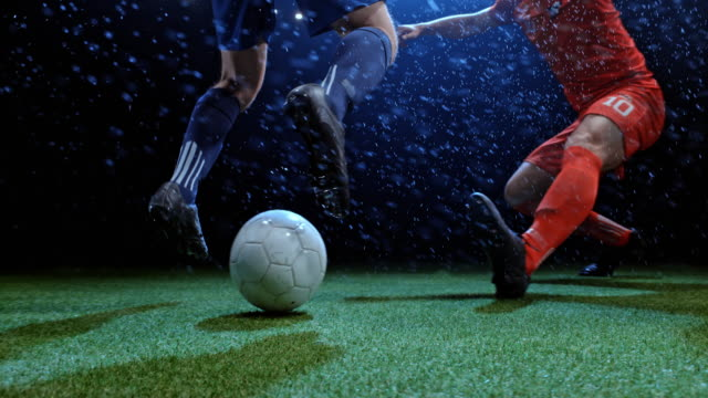 vídeos de stock e filmes b-roll de speed ramp soccer player dribbling his opponent trying to tackle him in rain - football