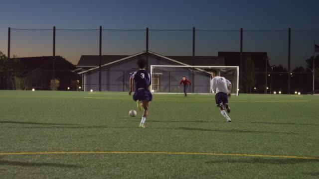 fußball-spieler dribbeln vorbei an verteidiger und erzielte dabei ein tor - spielfeld stock-videos und b-roll-filmmaterial