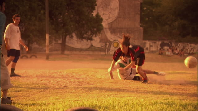 slo mo, ms, pan, soccer player falling over opponent while playing on field at sunset, buenos aires, argentina - competizione video stock e b–roll