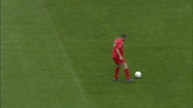 HA WS Soccer player in red uniform stopping ball with foot as it moves downward/ Players passing ball / Goalie stopping flying ball and rolling across ground/ Sheffield, England