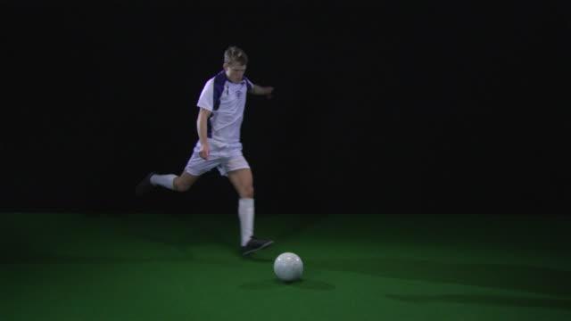 slo mo ws soccer player kicking ball / berlin, germany - 蹴る点の映像素材/bロール