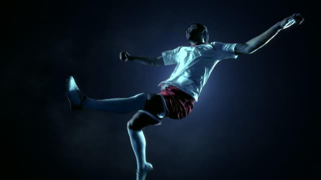 vídeos de stock e filmes b-roll de jogador de futebol no salto rematar a bola - retroiluminado