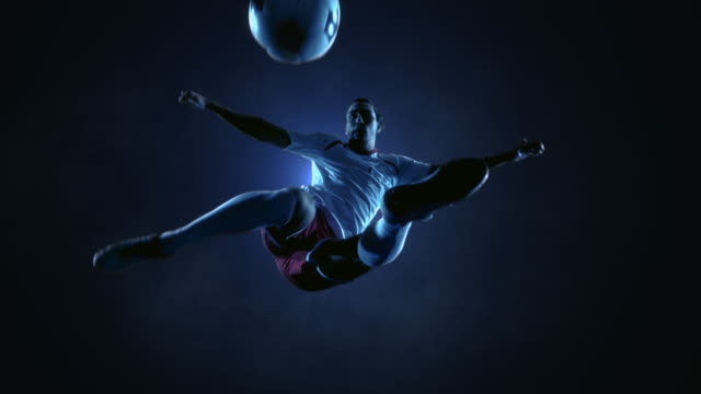 soccer player kicking ball in jump - sports equipment stock videos & royalty-free footage