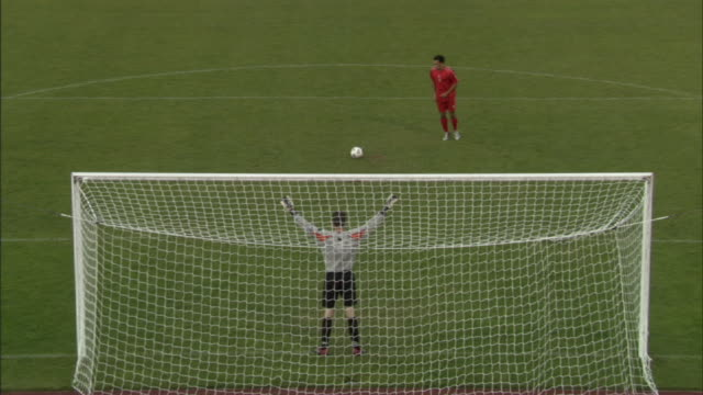 ha ws soccer player kicking ball into goal as goalie dives for it during penalty kick / sheffield, england, uk - soccer goal stock videos & royalty-free footage