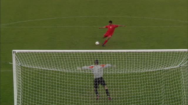 vidéos et rushes de ha ws zo zi ms soccer player kicking ball into goal during penalty kick, then joins teammates on field / sheffield, england, uk - gardien de but