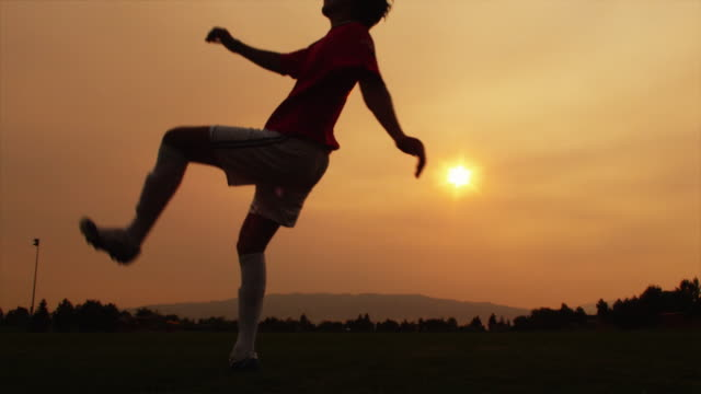 vídeos de stock e filmes b-roll de ms slo mo soccer player kicking ball mid-air at sunset / orem, utah, usa - orem