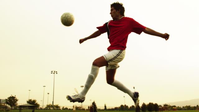 MS SLO MO Soccer player kicking ball on field / Orem, Utah, USA