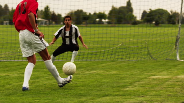 ws pan slo mo soccer player kicking ball on field / orem, utah, usa - tor konstruktion stock-videos und b-roll-filmmaterial