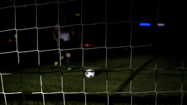 vídeos de stock, filmes e b-roll de soccer player kicking ball towards camera into a goal. football training at night. - marcar ponto