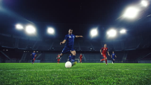 slo mo soccer player kicking the ball at football match - football strip stock videos & royalty-free footage