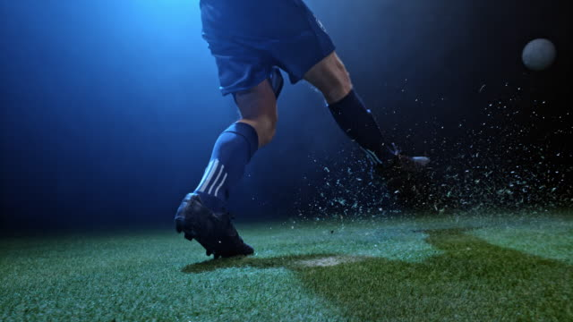 vídeos de stock, filmes e b-roll de slo mo soccer player kicking the ball in the arena at night - futebol