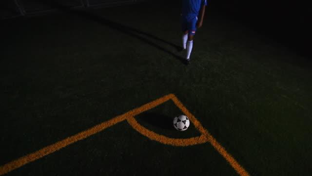 A soccer player kicks a ball.