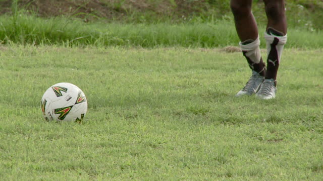 a soccer player kicks the ball during practice in ghana. available in hd. - ghana stock videos & royalty-free footage