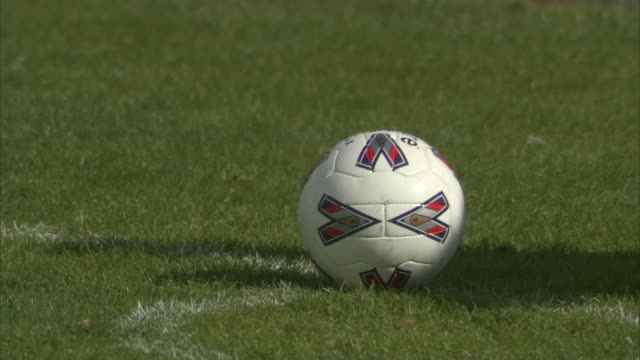 CU Soccer player placing ball on field, then kicks and runs after it / Sheffield, England, UK