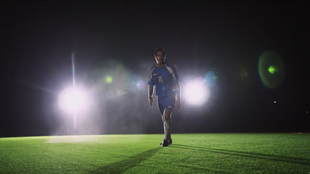 slo mo. soccer player runs towards the camera to kick a ball during a nighttime match - defender soccer player stock videos and b-roll footage