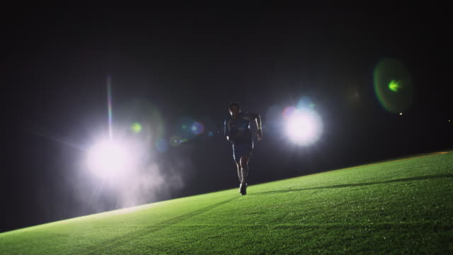 SLO MO. Soccer player runs towards the camera to kick a ball during a nighttime match