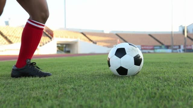 Fußball Spieler zeigen Beinarbeit und Fußballspieler treten und schießen Ball aufs Tor in Zeitlupe