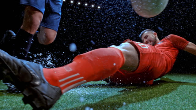 speed ramp soccer player slide tackling the opponent in the rainy field at night - football点の映像素材/bロール