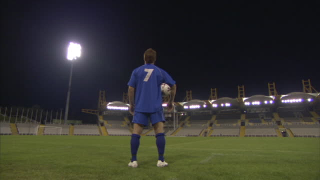 LA WS Soccer player standing in empty stadium at night / Sheffield, England, UK