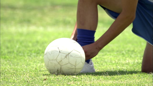 a soccer player ties his cleat and begins kicking a soccer ball on the grass. - tie stock videos & royalty-free footage