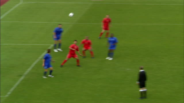 HA WS Soccer players crowded near goal as ball is thrown into play/ Red team player heading ball into goal/ Sheffield, England